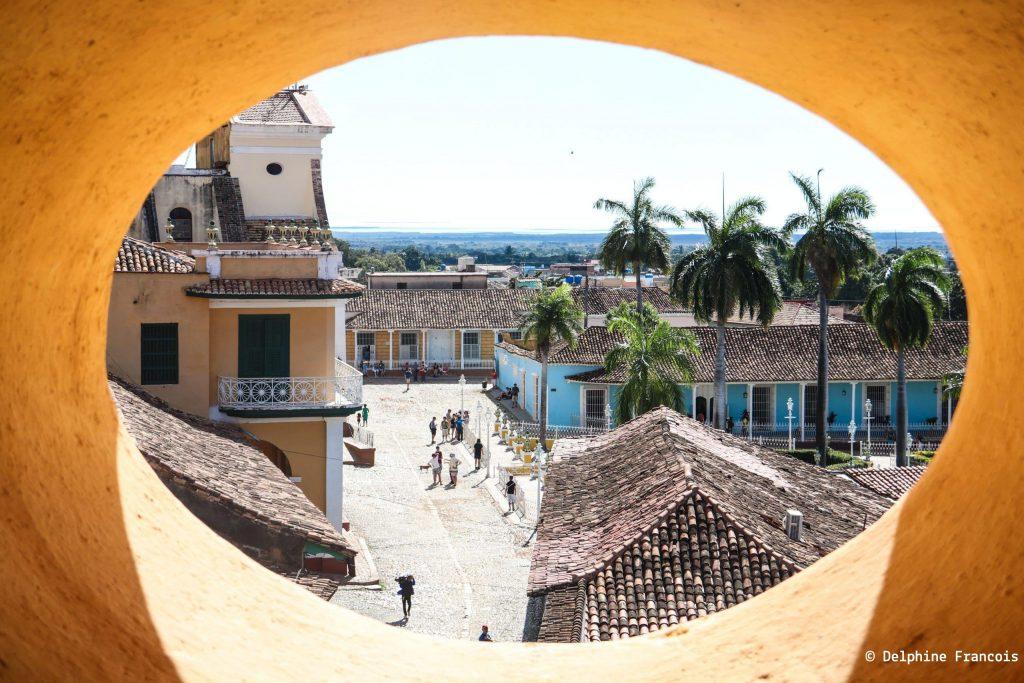 Vue sur les rues de Trinidad à travers un trou dans un mur ocre