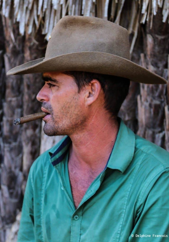 homme cubain de profil avec un cigare qui se consume dans la bouche