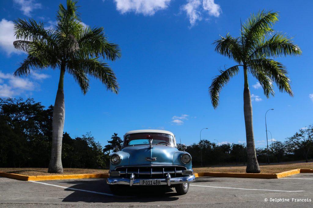 Voiture de collection bleue garée entre deux palmiers sous ciel bleu