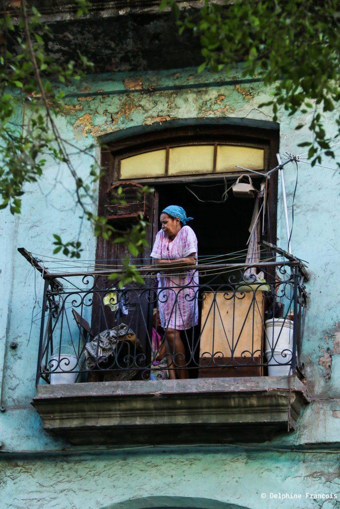 Femme en blouse rose regardant depuis son balcon la rue dessous