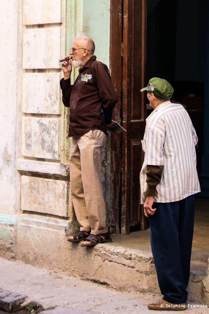 hommes devant une porte fumant un cigare