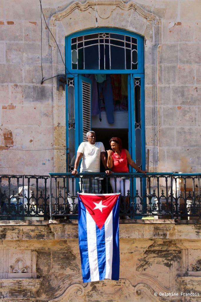 couple au balcon d'où pend un grand drapeau cubain