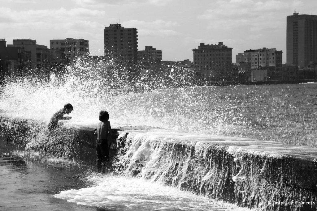 deux jeunes enfants éclaboussés par une vague passant au dessus d'un mur