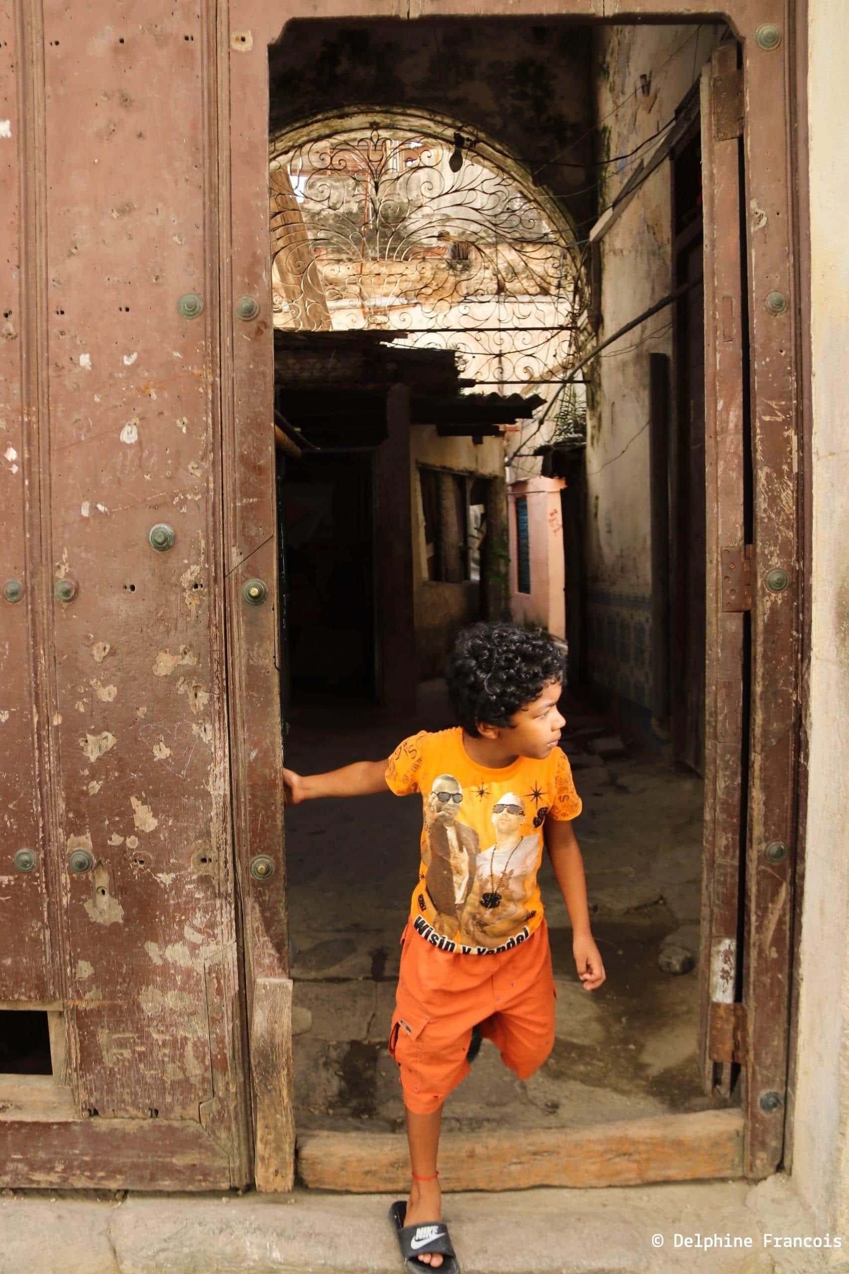 Enfant sortant d'une porte cochère et regardant dans la rue