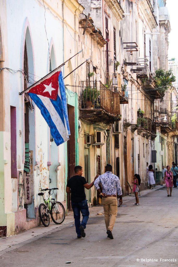 deux hommes avançant dans la rue sous un drapeau cubain