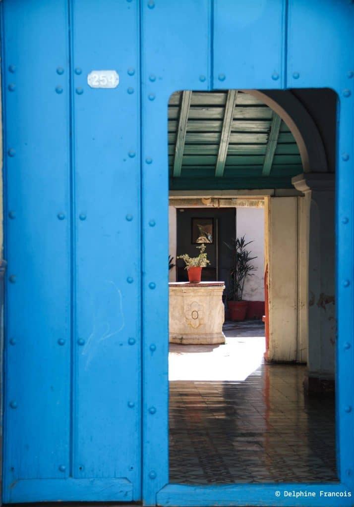 porte d'entrée bleue ouverte sur cour intérieure d'une maison traditionnelle cubaine