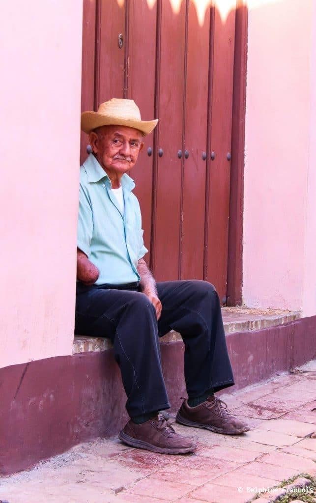 Vieil homme avec chapeau assis devant une porte rouge avec regard au loin