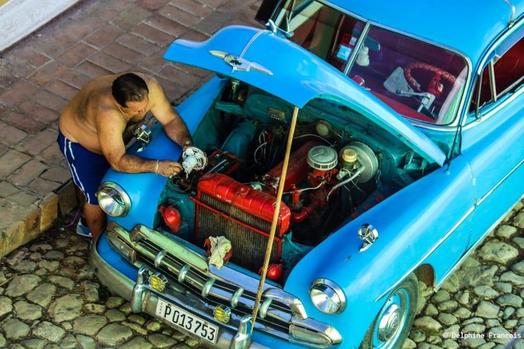 homme penché sur le capot ouvert d'une vieille voiture