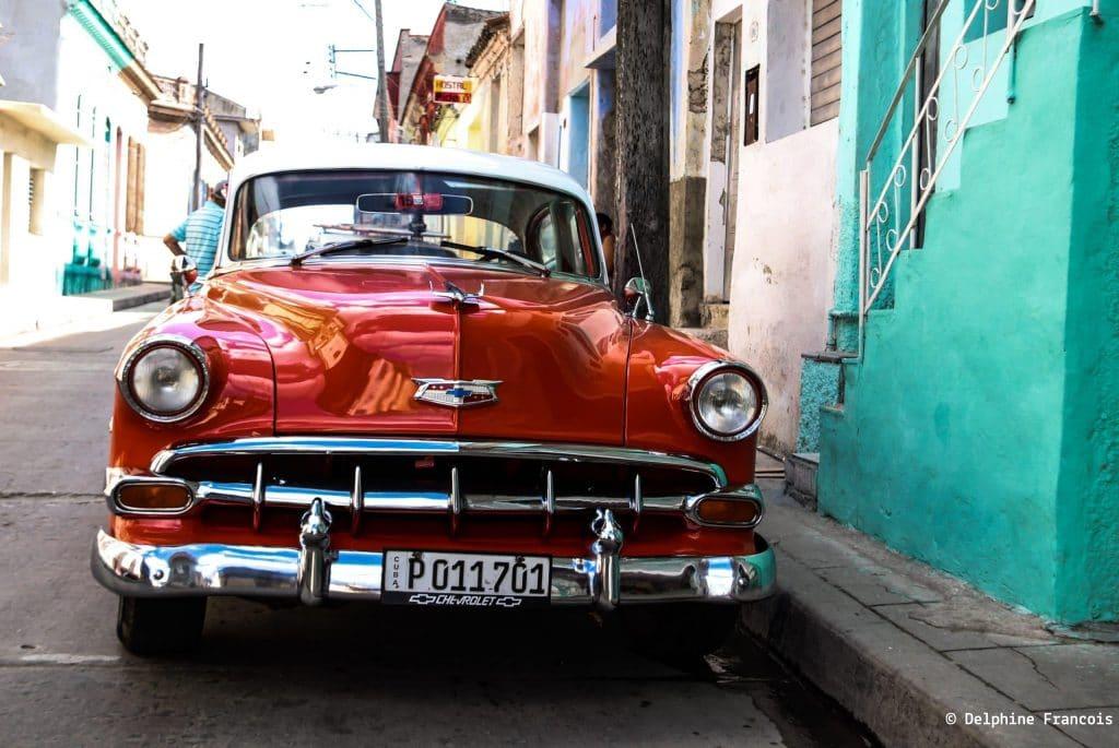 rutilante voiture rouge de collection garée dans une rue