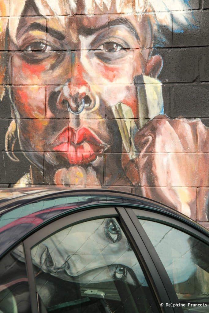 Graffitis représentant deux visages de femmes dont l'un se reflète dans la vitre d'une voiture