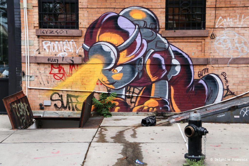 Graffiti représentant un garçon avec casque de mineur penché sur un trou